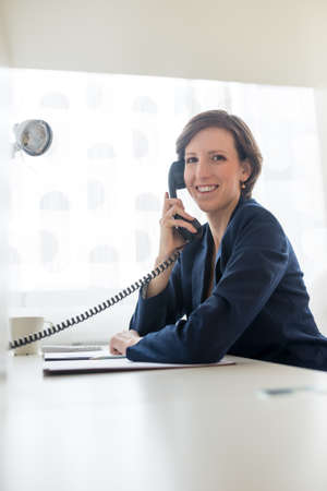 customer assistant: Pretty businesswoman in blue suit smiling as she  calling someone through telephone at her worktable conceptual of a call center or business communication. Stock Photo