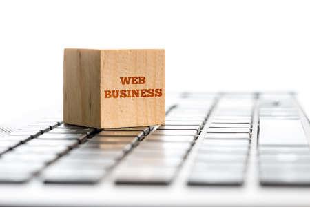コンピューターのキーボードの上に座って Web ビジネス サイン木製キューブ。現代グローバリゼーションとオンライン ビジネスの概念。