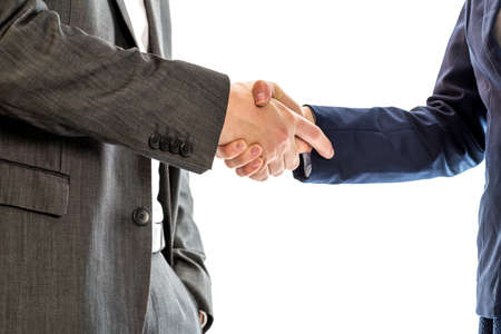 deal in: Confident relaxed businessman with his hand in his suit pocket shaking hands with  businesswoman to conclude a deal, agreement, partnership or in congratulations.