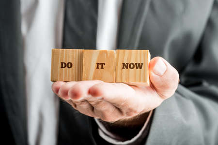 encouraging: Closeup of personal motivator holding three wooden cubes aligned on the palm of his hand saying Do it now encouraging you to take action in your life and make your dreams come true.