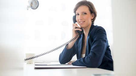 Vriendelijke aantrekkelijke jonge zakenvrouw praten aan de telefoon als ze zit op haar bureau in het kantoor te draaien om te lachen naar de camera.