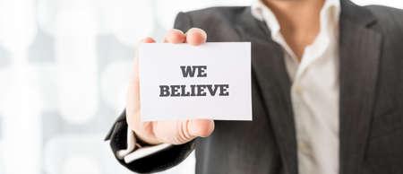 believe: Profesor sosteniendo una tarjeta blanca con Creemos firmar en él, de cerca formato de banner horizontal de la mano.
