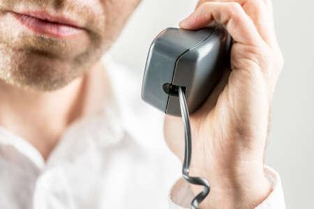 Een ongeschoren man luisteren naar een telefoongesprek met de hoorn in zijn hand, richten naar de ontvanger.