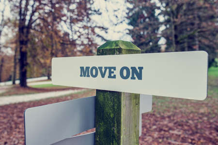 put forward: Move on concept with a rural signboard in an autumn landscape with the words - Move on - at an angled perspective. With retro effect faded look.