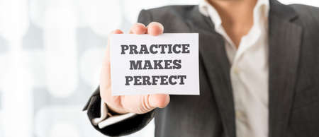 professional practice: Personal mentor holding up a white card with a reminder Practice makes perfect.
