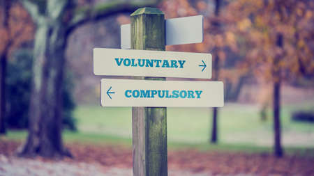 forced perspective: Signpost in a park or forested area with arrows pointing two opposite directions towards Voluntary and Compulsory, retro effect faded look. Stock Photo