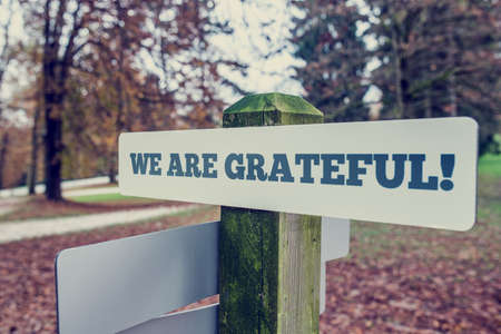 gratified: We Are Grateful concept with an angled signboard with the words on a rustic wooden pole in an autumn landscape, with a vintage style filter effect.