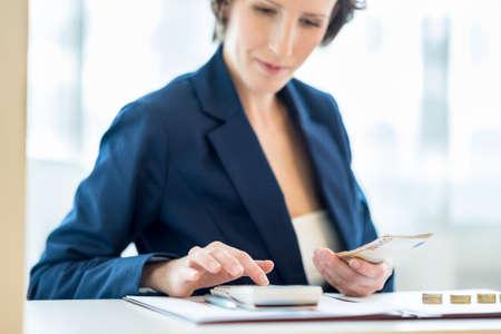 Geschäftsfrau, die auf Rechner mit Goldmünzen auf dem weißen Schreibtisch. Konzentrieren Sie sich auf die Hand und Euro-Banknoten.