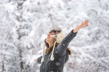 outspread: Young woman celebrating winter standing outdoors in a wintry garden in falling snow with her arms outspread.