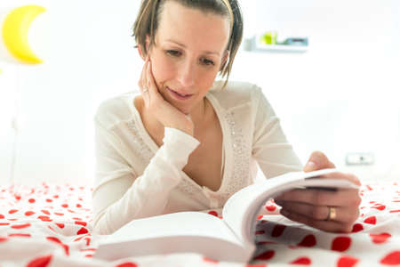 bedspread: Young brunette reading an interesting novel or studying comfortably lying on her red and white polka dot bedspread.