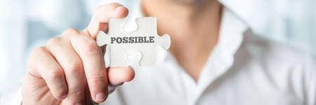 probable: Businessman holding puzzle piece with Possible text in a conceptual image for positive attitude in resolving challenges and problems, close up horizontal banner format of his hand.