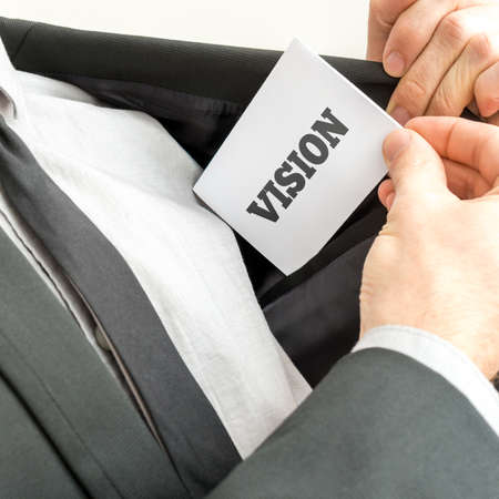 by placing: Businessman removing or placing a white card with word Vision in the inner pocket of his suit jacket.