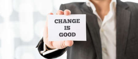business change: Close up Businessman in Business Suit Showing Small White Card with Change is Good Message.