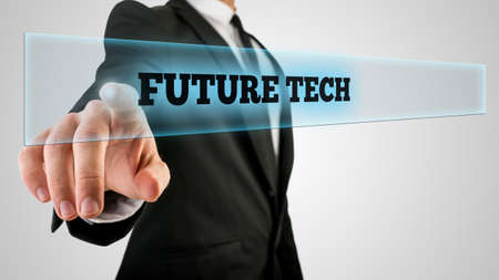 modernization: Conceptual Businessman in Black Business Suit Clicking a Glass with a Glowing Future Tech Label, Captured in Close up on a Gray Background. Stock Photo
