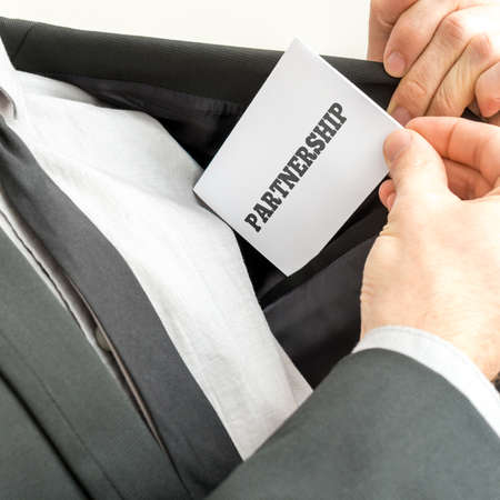 Closeup of businessman placing a business card with word Partnership in the inner pocket of his suit jacket. photo