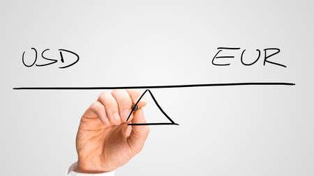 eur: Conceptual image of the hand of a man drawing a seesaw in equilibrium with the text EUR - USD showing a balance between the two currencies.