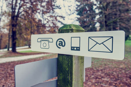 correspond: Retro vintage style image of a contact signboard with icons for telephone, email, mail and mobile outdoors in an autumn park. Stock Photo