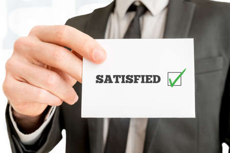 SATISFIED: Customer feedback - Satisfied - concept with a businessman holding up a card with a ticked check box from a survey or feedback report and the word Satisfied, close up of his hand. Stock Photo