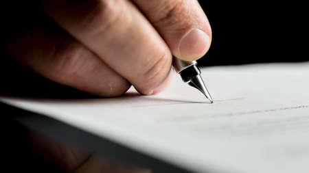 사업가 서명 또는 nibbed 샘 펜을 사용하여 흰 종이에 문서를 작성하는 손의 매크로 샷입니다. 스톡 콘텐츠