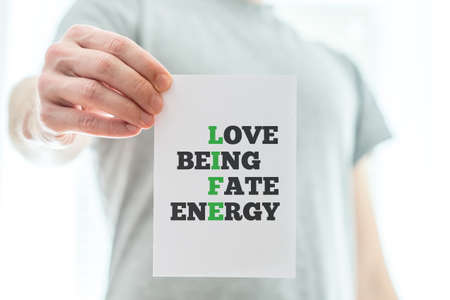elan: Conceptual White Paper Hold by Man with Life Text in Green with Other Related Words, Emphasizing Love, Being, Fate and Energy. Over Bright Background. Stock Photo