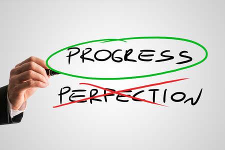 Concetto di perfezione con un uomo d'affari che attraversa attraverso la parola scritta a mano Perfezione in rosso mentre squillo progressi nella verde concettuale di sacrificare la perfezione per lo sviluppo e il progresso - Progress. Archivio Fotografico - 38671398