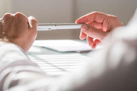 papier a lettre: Gros plan d'affaires appuyant son bras sur la table tout en tenant un stylo avec ses deux mains par une journ�e ensoleill�e.