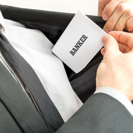 Close up of the hand of a banker displaying a card reading - Banker - as he removes it from the pocket of his jacket. photo