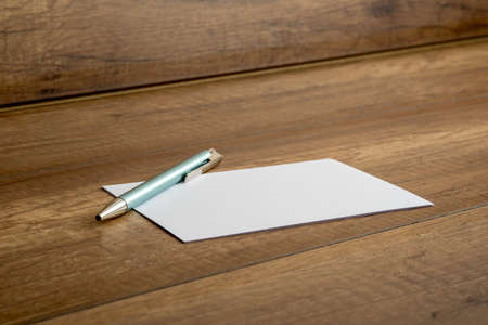 oblique: Stylish ballpoint pen and blank white card or note lying on a wooden table, low angle oblique view. Stock Photo