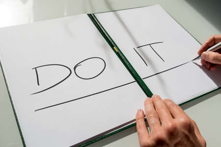 not open: Do It concept with the hand of a man writing the words in large capital letters across an open notebook conceptual of - do not procrastinate, do it immediately. Stock Photo