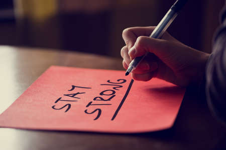 Conceptual Handwritten Stay Strong Phrase on red Sticky Note on Top of Wooden Table, Captured in Close up.