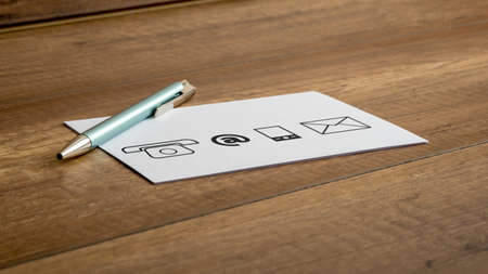 Ballpoint pen and four different contact icons printed on a white card or note lying on a wooden table.