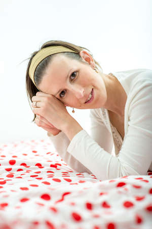 leaning on elbows: Attractive young woman wearing an headband in her hair leaning on her elbows on a colourful duvet with red polka dots smiling at the camera.
