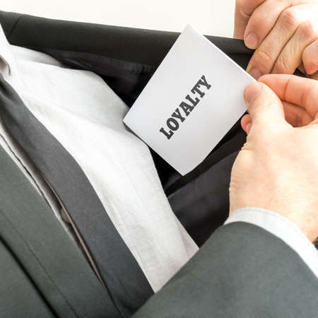 loyalty: Businessman showing a white card reading - Loyalty - as he withdraws it from the pocket of his suit jacket.