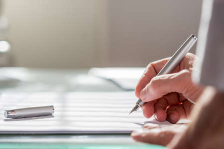 View past the arm of a colleague of a businessman writing on a document with a fountain pen, close up focus to the hand.