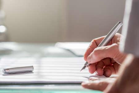 escritura: Ver más allá del brazo de un colega de un empresario por escrito en un documento con una pluma estilográfica, de cerca foco a la mano.