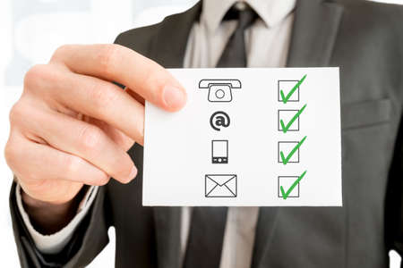 Communications concept with a businessman holding up a checklist with the icons for telephone,email, mobile phone and website ticked with green check marks, close up of his hand holding a card.
