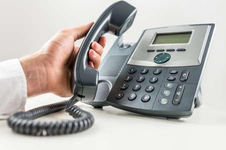 Primer plano de negocios que sostiene un receptor de teléfono a punto de hacer una llamada en el teléfono de línea fija. Conceptual de servicio al cliente o telemarketing.