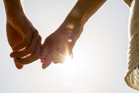 Close up Hands of Romantic Couple Holding Together with Sun Rays on a White Sky.
