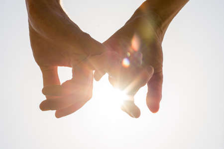 Couple holding hands towards the sun with bright sun flare between the silhouetted fingers on a pale blue sky, close up view in a conceptual image.