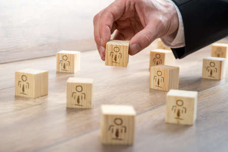 arrange: Customer-Managed Relationship Concept - Businessman Arranging Small Wooden Blocks with Symbols on the Table.