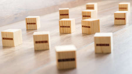 metaphoric: Conceptual Small Wooden Cubes on Top of a Table with Business Texts. Captured in Close up. Stock Photo