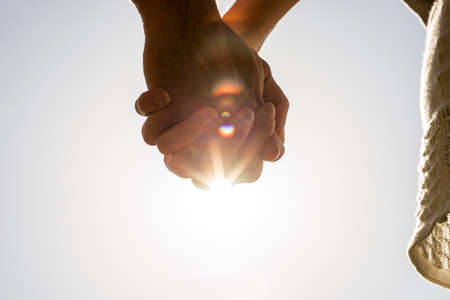 Clasped hands of a young romantic man and woman against a bright sun flare with copyspace, conceptual image of love and friendship.