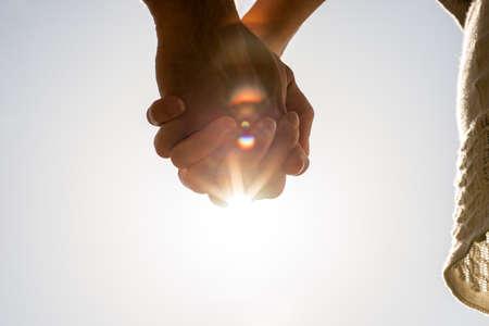manos entrelazadas: Manos entrelazadas de un hombre romántico y una mujer jóvenes contra un sol brillante llamarada con copyspace, imagen conceptual de amor y amistad. Foto de archivo