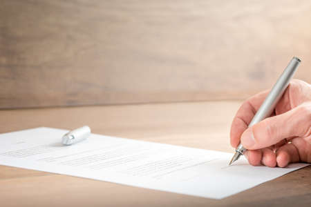 legal document: Close up Hand of a Businessman Signing a Contract Document on Top of a Wooden Table.