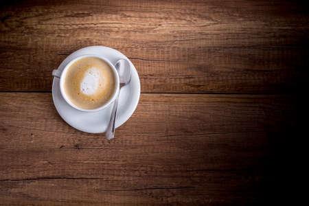 木製のテーブルの上に立ってたての芳香族カプチーノのおいしいカップの平面図です。