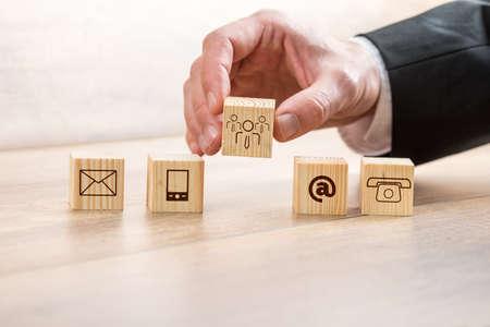 Chiuda sull'uomo d'affari che sistema i cubi di legno con i simboli di cura del cliente e del contatto sopra una Tabella. Archivio Fotografico - 39384198