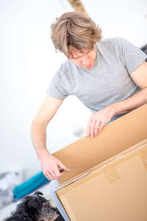 tilted view: Man in casual clothes kneeling on the floor unpacking a flat cardboard carton, tilted angle close up view.
