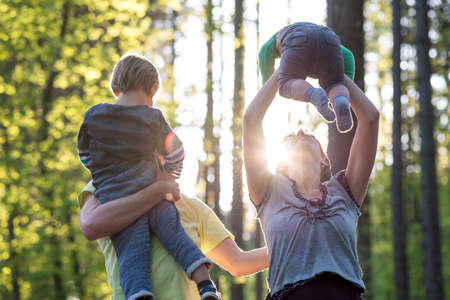 high life: Parents playing with their two young children outdoors in a green spring forest backlit by a glowing sun as they enjoy the tranquility of nature. Stock Photo