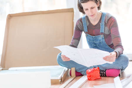Young woman in dungarees sitting on the floor reading instructions on how to assemble recently delivered flat pack furniture.