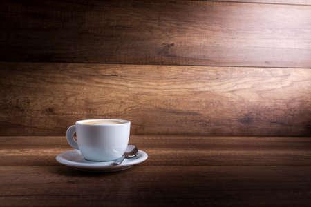taza cafe: Copa del delicioso dulce capuchino caliente se coloca en una mesa de madera en un rayo de luz sobre un fondo de madera r�stica con un mont�n de copyspace. Foto de archivo